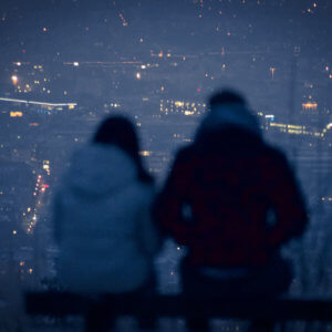 man and woman sitting on bench during night time